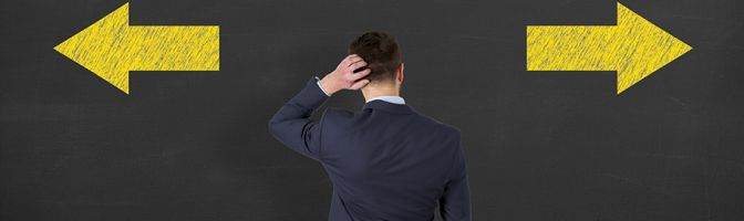 Confused businessman - people feeling confusion and chaos. Indecisive, disorientated and bewildered man stressed with headache over decision making. Young Man on blackboard background
