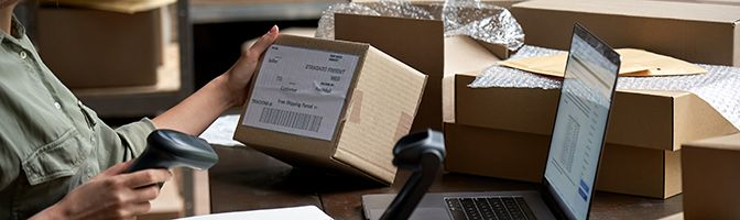 Entrepreneur scans label on box that is ready to ship for online business.