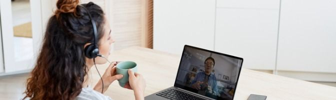 Woman holding a cup and wearing headphones while on a video conference call