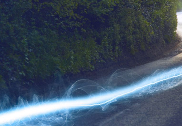 streaks of light blazing down a rural paved street