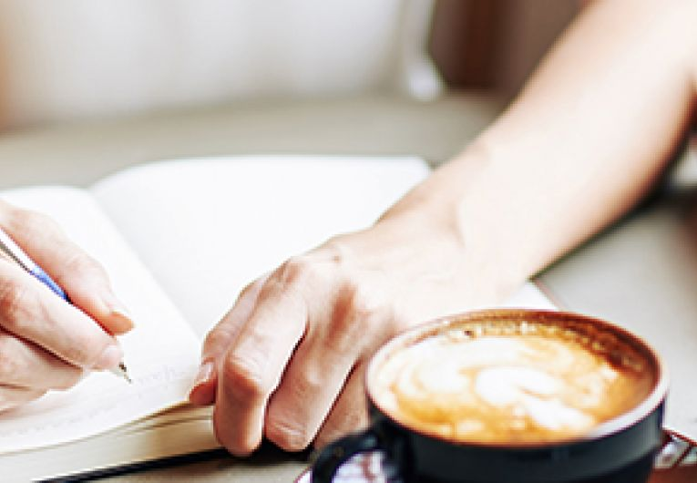 Closeup of a person writing in a journal with a cup of coffee and glasses on a table.