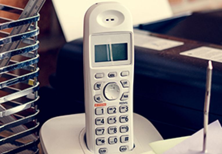 Image of a business landline phone in its cradle.