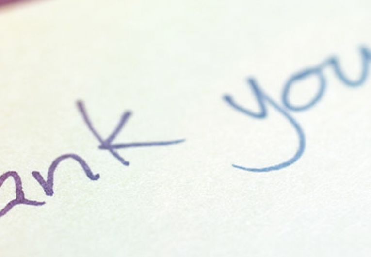 close up of someone writing thank you on a piece of paper