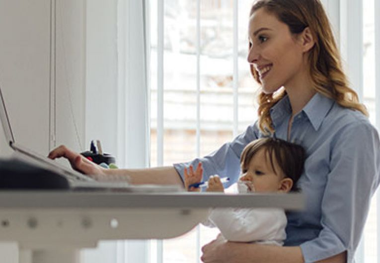 woman working at desk with baby on lap