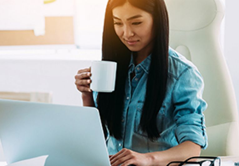 Entrepreneur works in front of a laptop while holding a mug in her hand.