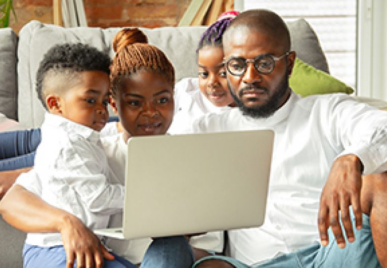 Family of four relax in their living room watching a movie through a laptop.