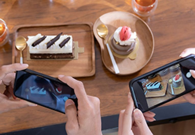 Two people take a photo with their mobile phones of a plate of dessert and beverage.
