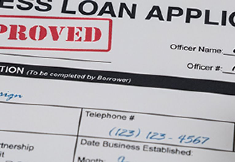 "Business loan application shown with a red ""Approved"" stamp."