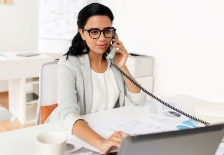 Home business owner talking on the phone while viewing a laptop