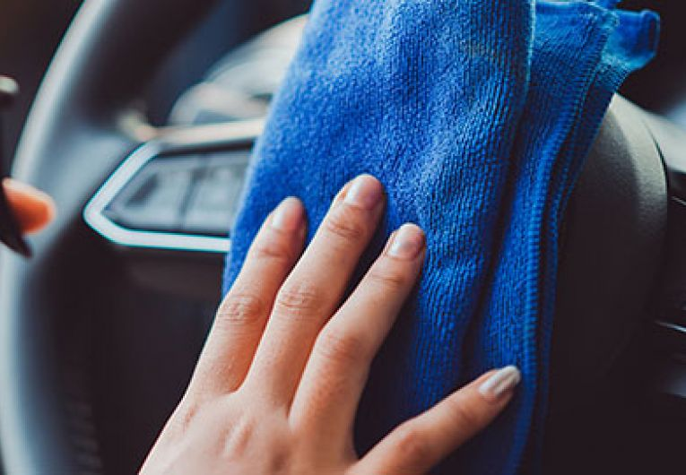 close up of someone cleaning their steering wheel with a blue rag