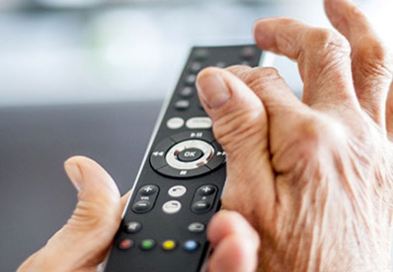 close up of a person using a tv remote