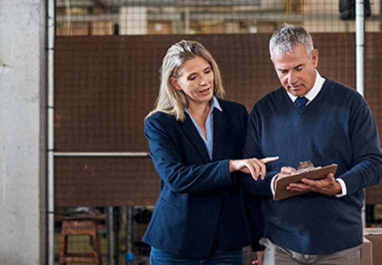man and woman discussing something in a warehouse