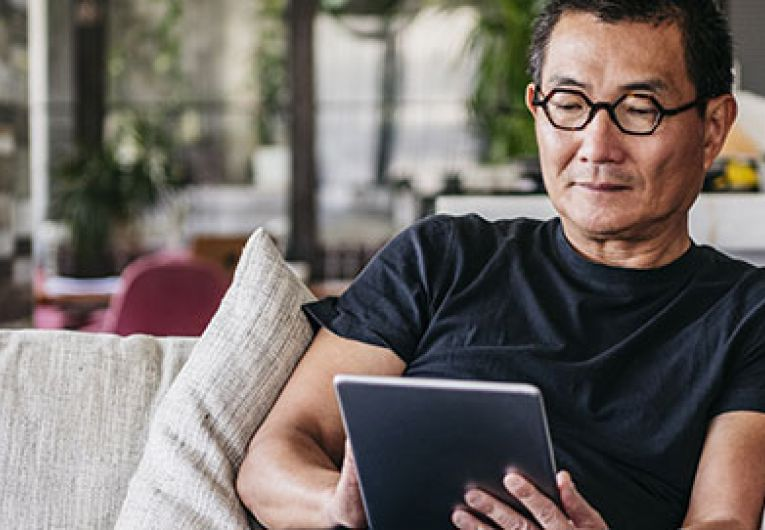 man sitting on couch using a tablet