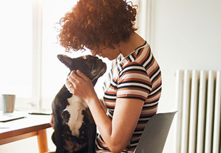 Woman holding dog at home office
