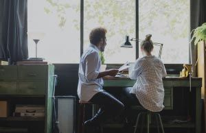 two coworkers sitting on stools working at a desk