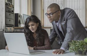 two smiling coworkers in an office looking at a laptop screen